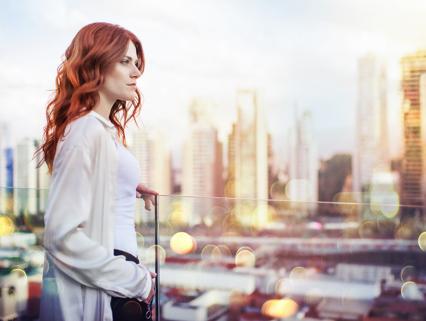 mujer de cabello rojo en balcon vista a la ciudad distrito armida